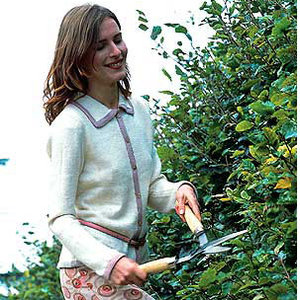 Model wearing contrast trim knitted jacket and doing gardening