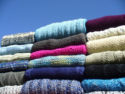 Pile of multi-coloured knitted jumpers